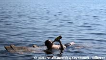 dpatopbilder - 24.06.2018, Russland, Togliatti. Fußball, WM: Ein Mann badet in der Wolga und trinkt, auf einem Brett im Wasser liegend, aus einer Flasche. Foto: Laurent Gillieron/KEYSTONE/dpa +++ dpa-Bildfunk +++ |