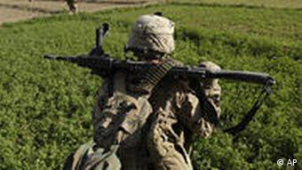 US Marines move in formation through farm fields