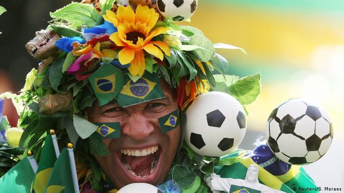 Torcedor brasileiro enfeitado com bandeirinhas do Brasil, flores e bichos antes da partida contra o México pela Copa de 2018