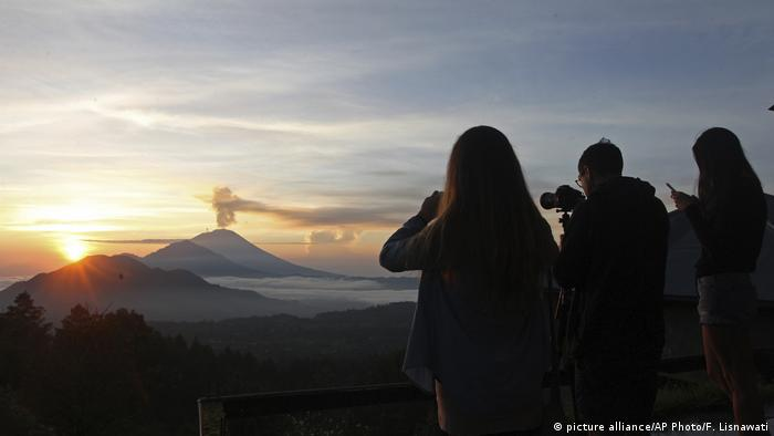 Spectators watch Mount Agung during a sunrise