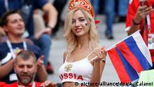 01.07.2018, Russland, Moskau: Fußball: WM, Finalrunde, Achtelfinale: Spanien - Russland im Luschnikistadion. Ein weiblicher Fan von Russland steht vor Spielbeginn mit russischen Nationalflaggen auf der Tribüne. Foto: Antonio Calanni/AP/dpa +++ dpa-Bildfunk +++  