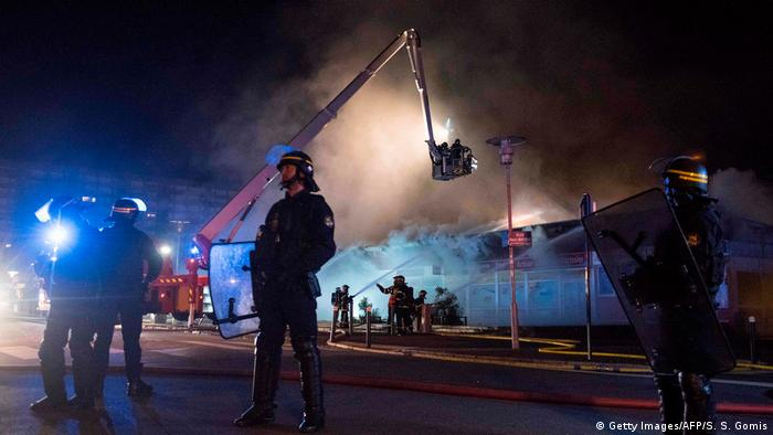 Police secure perimeter of shopping mall as firefighters attempt to put out blaze