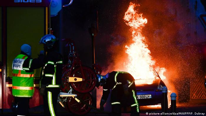 Firefighters attempt to extinguish a burning car in Nantes, on the night of July 3-4.