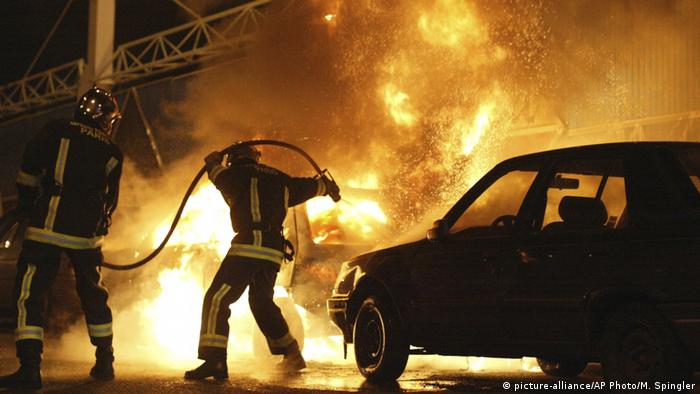 Firefighters attempt to extinguish burning cars set alight during 2005 protests in the Paris banlieue Clichy-sous-Bois