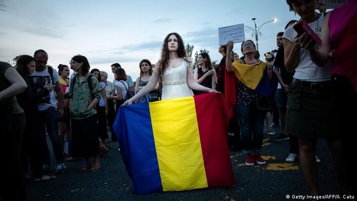 A woman holds a flag of Romania during a gathering in front of the Romanian Prime Minister's office building