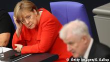 05.07.2018 BERLIN, GERMANY - JULY 05: German Interior Minister and leader of the Bavarian Social Union (CSU), Horst Seehofer, speaks at the last session of the Bundestag before the sumer break as German Chancellor and leader of the German Christian Democratic Union (CDU) Angela Merkel (in red) looks on on July 5, 2018 in Berlin, Germany. Merkel and Seehofer recently reached a hard-wrung compromise over migration policy, though uncertainty remains over how the compromise will be implemented. (Photo by Sean Gallup/Getty Images)