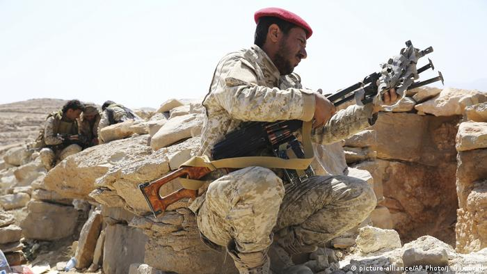 A Yemeni soldier allied to the country's internationally recognized government uses his machine gun on the outskirts of Sanaa, Yemen in February 2018