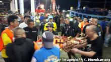 Thai rescue and paramedic personnel attend to rescued passengers of capsized tourist boat in rough seas at a port in Phuket on July 5, 2018. - Dozens of passengers are missing after a boat capsized as high winds whipped up rough seas off the Thai tourist island of Phuket, officials said late July 5. (Photo by Kritsada MUENHAWONG / AFP) (Photo credit should read KRITSADA MUENHAWONG/AFP/Getty Images)