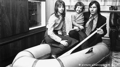Family sitting in a rubber boat in their living room in 1977