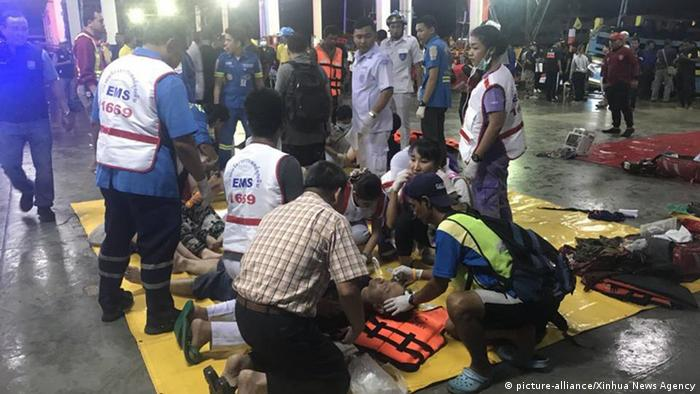 First aid teams help survivors pulled from the water off Phuket