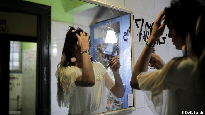 A transgender woman applying makeup in front of a mirror