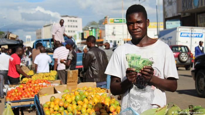 A young street vendor holding up a stack of bills at a fruit stall