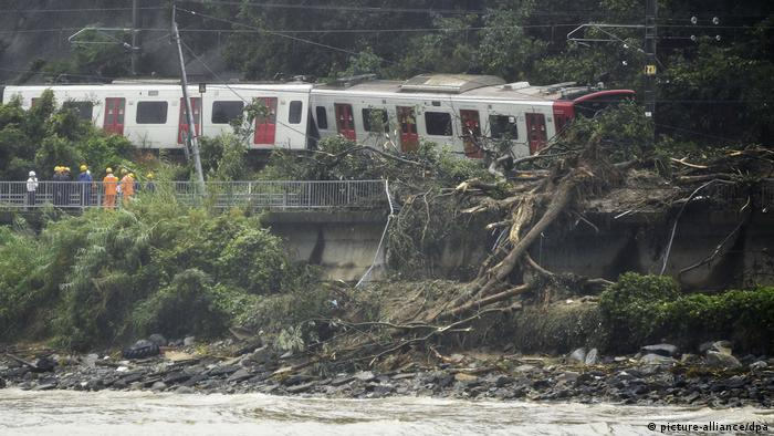A landslide buried a railway track under mud and trees while knocking a train off the rails.