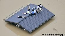 07.07.2018, Japan, Kurashiki: Menschen liegen auf dem Dach eines Gebäudes, in einer überfluteten Region steht, und warten auf ihre Evakuierung. Wegen sintflutartiger Regenfälle im Westen Japans mussten mindestens 440.000 Menschen ihre Häuser und Wohnungen verlassen. Foto: Shingo Nishizume/Kyodo News/AP/dpa +++ dpa-Bildfunk +++ |