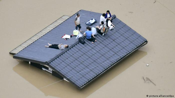 Only the rooftop of this house is above water, as where six people with a handful of belongings wait to be rescued.