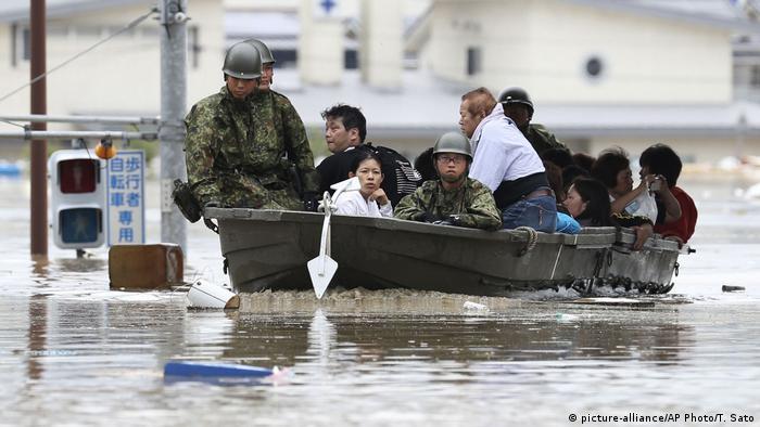 Japanese soldiers evacuate stranded residents in Kurashiki by boat.