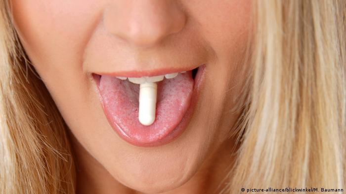 Frau hat eine Tablette auf der Zunge (picture-alliance/blickwinkel/M. Baumann)