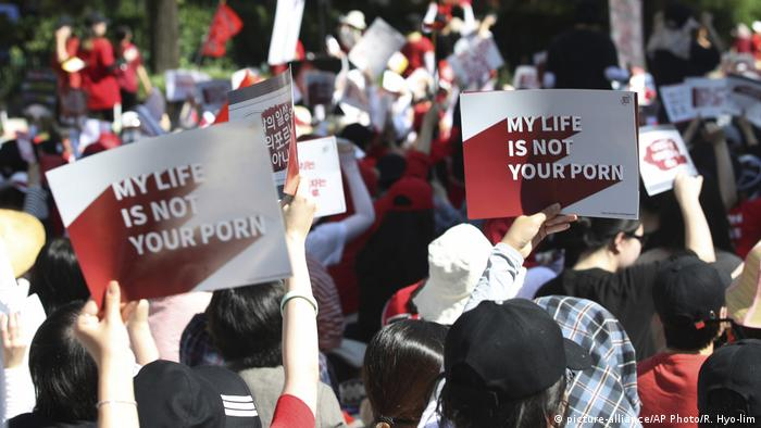 South Korean women hold up placards to protest rise in sexual violence