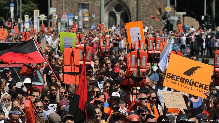 Protesters hold up life jackets and signs at a protest in Berlin to support migrant rescue operations in the Mediterranean Sea (picture-alliance/dpa/J. Carstensen)