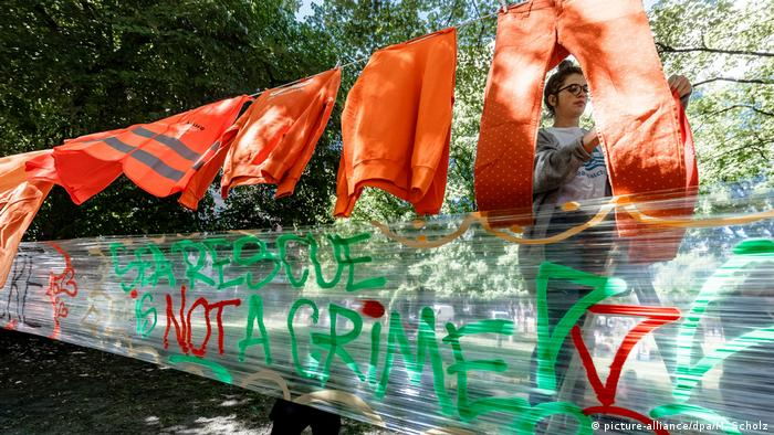 A woman sets up a sign reading: Sea rescue is not a crime during a protest in Hamburg in support of migrant rescue operations in the Mediterranean Sea (picture-alliance/dpa/M. Scholz)