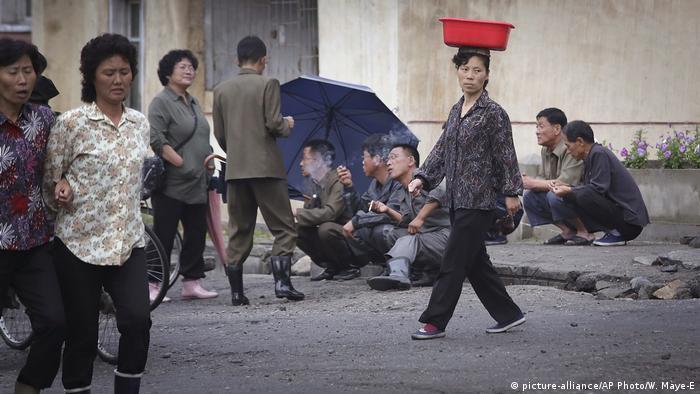 A North Korean woman balances a pail on her head