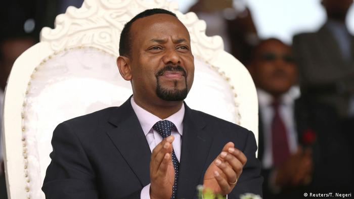 Abiy Ahmed claps while seated on an elaborate white chair (Reuters/T. Negeri)