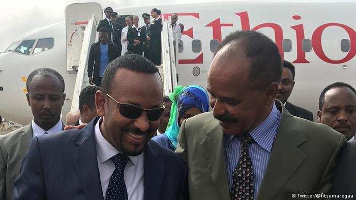 Ahmed and Asmara walk shoulder to shoulder from an Ethiopian airline