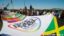 Pride marchers carry a massive banner with the flags of the world and a 'stop homophobia' segment.