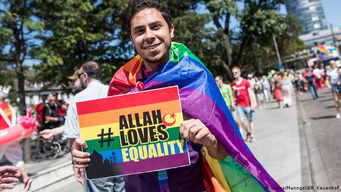 A young Muslim man, draped in a Pride flag, holds a sign that reads: Allah loves equality.