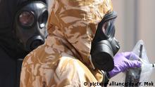 06.07.2018, Großbritannien, Salisbury: Zwei mit Schutzanzügen bekleidete Ermittler arbeiten hinter Stellwänden, die in der Rollestone Street aufgestellt wurden. Vier Monate nach dem Anschlag auf die Skripals sind wieder ein Mann und eine Frau lebensbedrohlich durch den Kampfstoff Nowitschok erkrankt. Foto: Yui Mok/PA Wire/dpa +++ dpa-Bildfunk +++