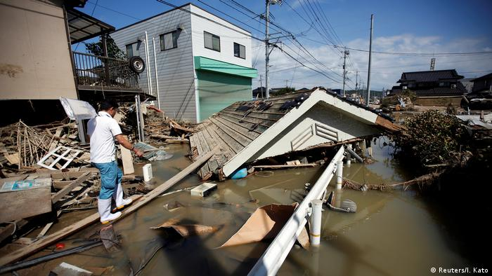 A local resident walks on submerged and destroyed houses in a flooded area in Mabi district of Kurashiki