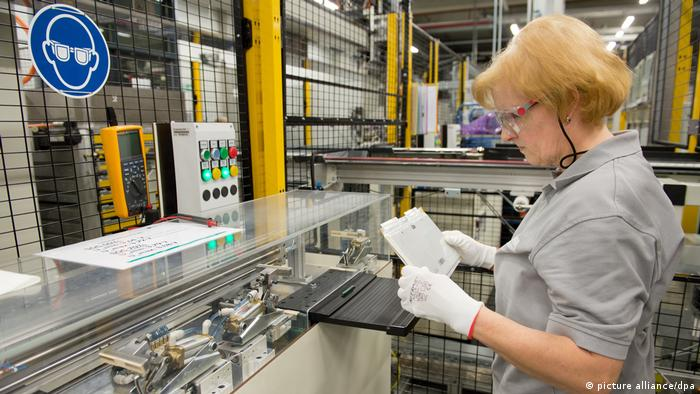 Worker inspecting battery cell at Daimler's Kamenz plant
