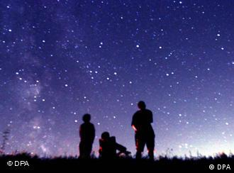 The silhouettes of people as they look up at the stars