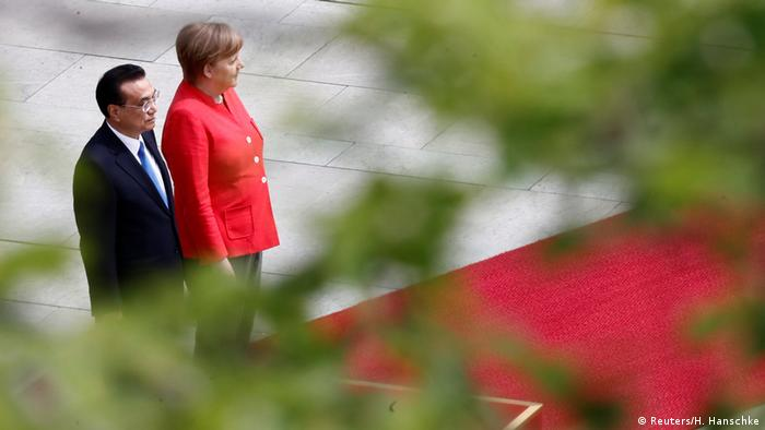 German Chancellor Angela Merkel and Chinese Prime Minister Li Keqiang review the guard of honour in Berlin on July 9 (Reuters/H. Hanschke)