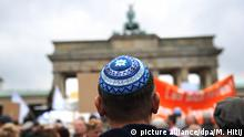 A man wears a kippa in front of the Brandenburg Gate (picture alliance/dpa/M. Hitij)
