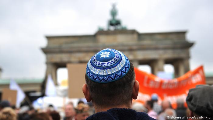 A man wears a kippa in front of the Brandenburg Gate