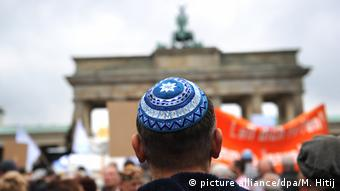 Участник акции в Берлине против антисемитизма в Германии