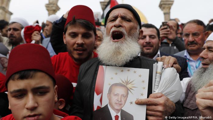 A man holds a sign of Erdogan and cheers admist a crowd