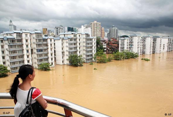 Eine Frau schaut von einem Hausbalkon auf eine Siedlung von Hochhäusern, die alle völlig vom Wasser umspült sind (Quelle: AP)