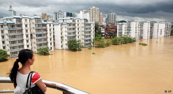 A woman looks at flood waters in Liuzhou in south China's Guangx region in 2009