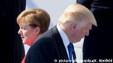 German Chancellor Angela Merkel walks by US President Donald Trump at a NATO summit in Brussels