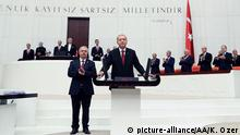 Recep Tayip Erdogan stands behind a podium as people applaud (picture-alliance/AA/K. Ozer)