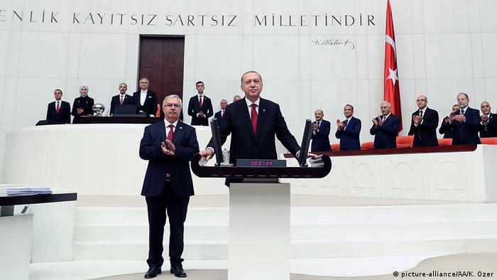 Recep Tayip Erdogan stands behind a podium as people applaud
