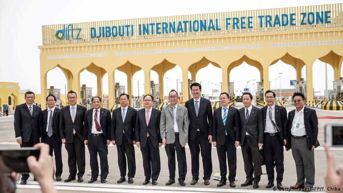 China Merchants Group members take pictures at the main gate of Djibouti International Free Trade Zone.