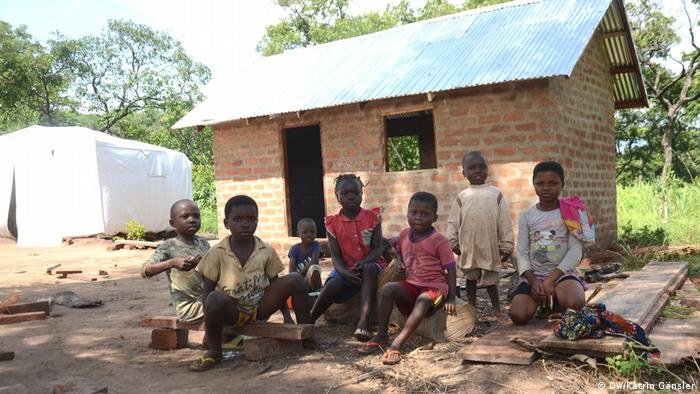 Cameroonian displaced children sitting before a half-built brick hut(DW/Katrin Gänsler)