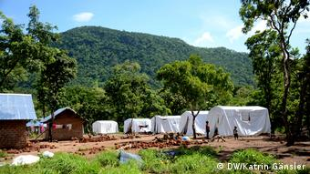 White tents and a few huts sit on a muddy field surrounded by trees