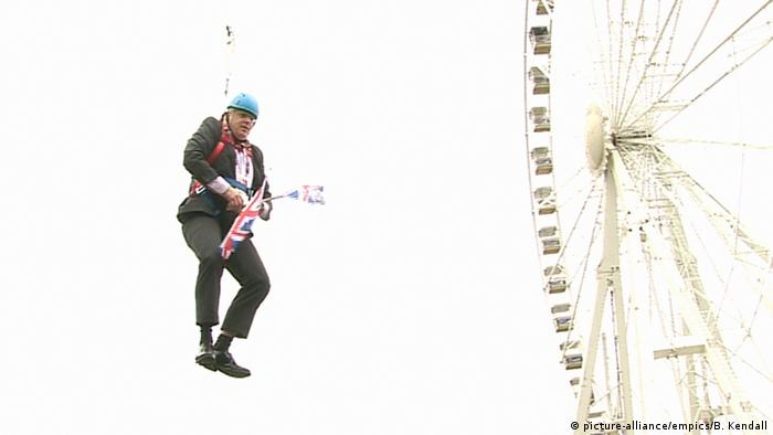 Boris Johnson holds a Union Jack and hangs from a zipwire
