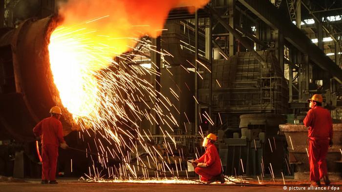 Drei Arbeiter stehen um einen Hochofen in einem Stahlwerk