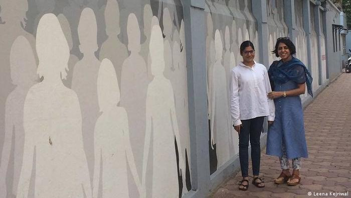 Leena Kejriwal stands in front of a wall painted with her stencils representing missing girls