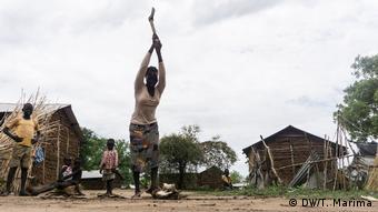 A woman chops wood outside